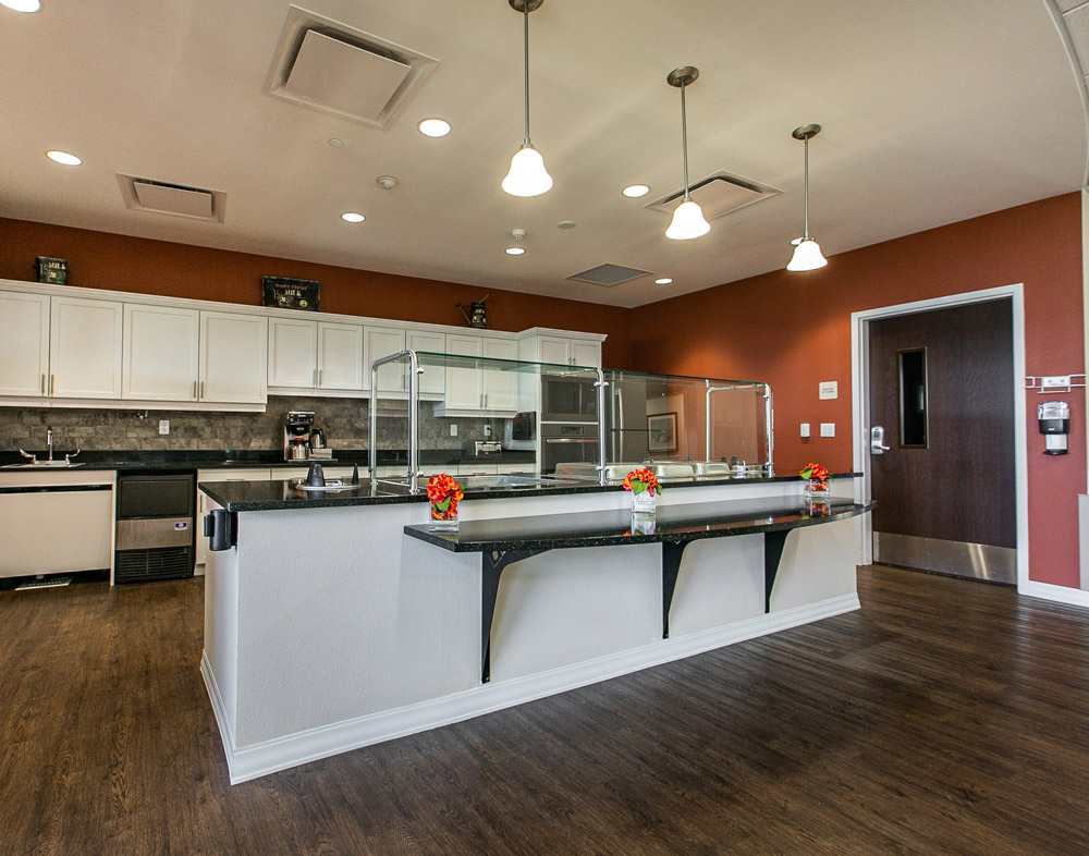 Hawkeye Care Center kitchen area with white cabinets and food serving area on a long island counter