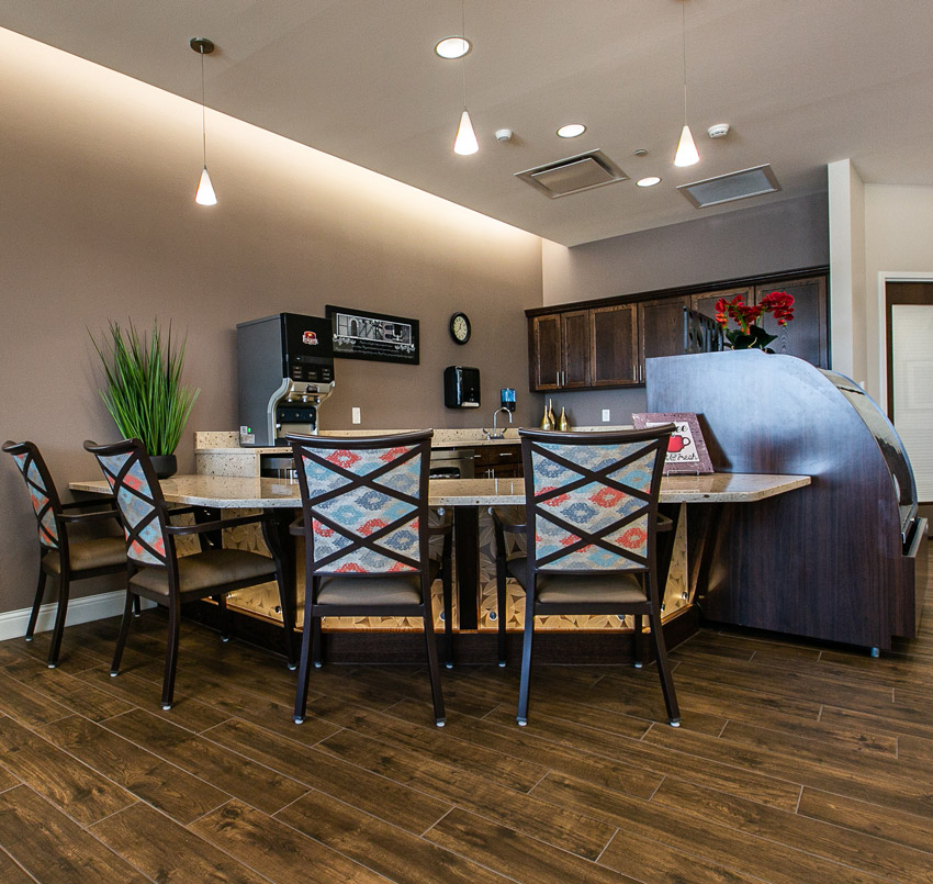 Hawkeye Care Center eating area with 4 chairs around a bar, which is in front of a kitchen area