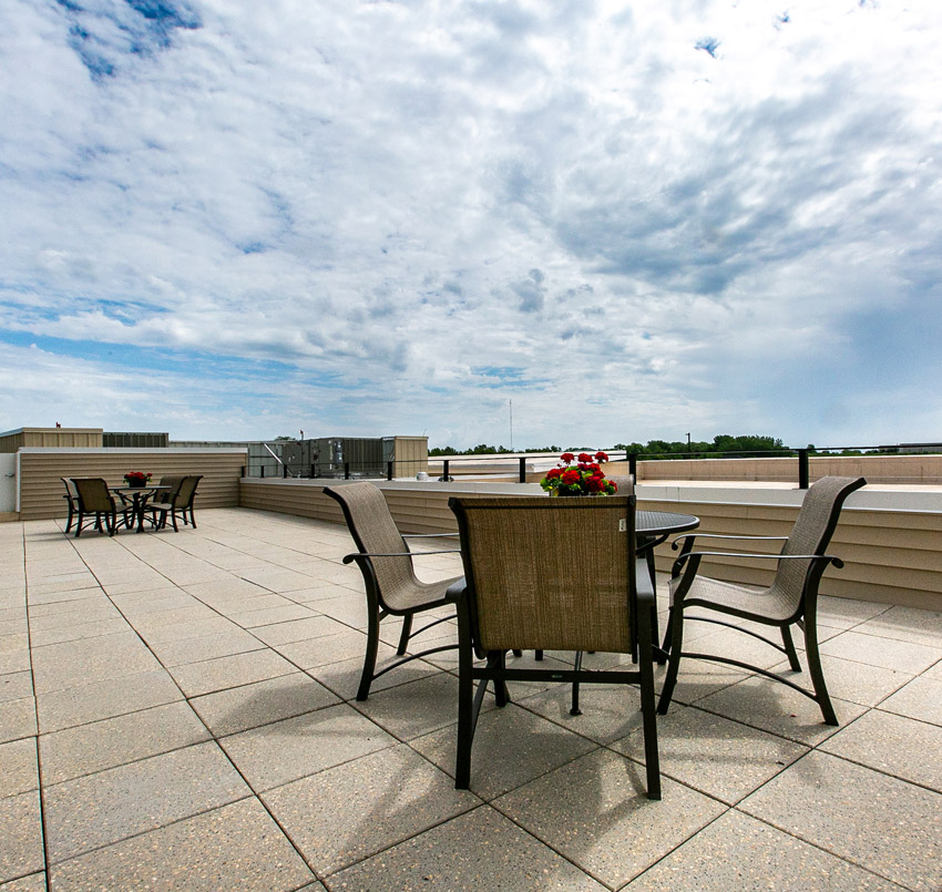 Hawkeye Care Center outdoor seating area on a balcony with two metal patio tables, each with 4 chairs, and red flowers on the center