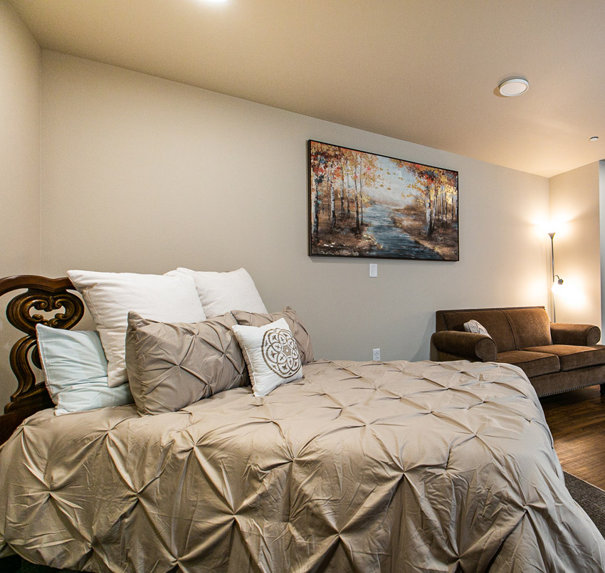 Hawkeye Care Center bedroom with a queen sized bed made up with beige comforter and several pillows, and a brown couch.