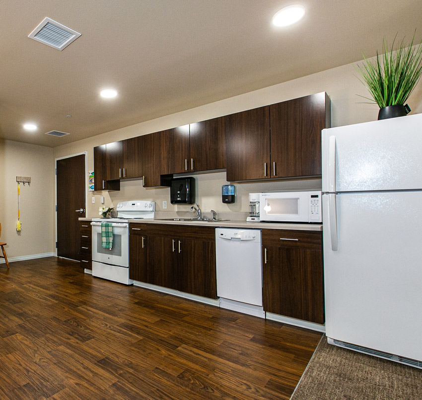Hawkeye Care Center in-room kitchen area with dark wood cabinets and white appliances.