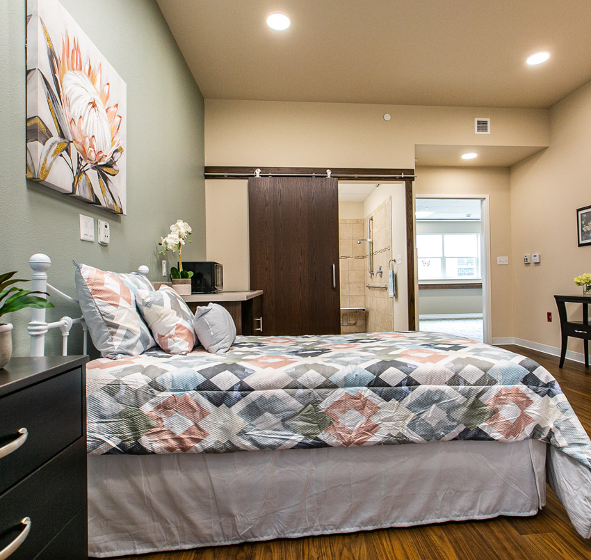 Hawkeye Care Center bedroom with a twin bed, and sliding door showing a part of the bathroom