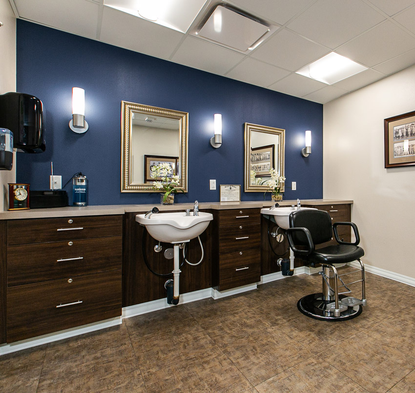 Hawkeye Care Center salon area with a dark blue wall, dark wood cabinets, two salon sinks, a salon chair, and two gold-colored framed mirrors.