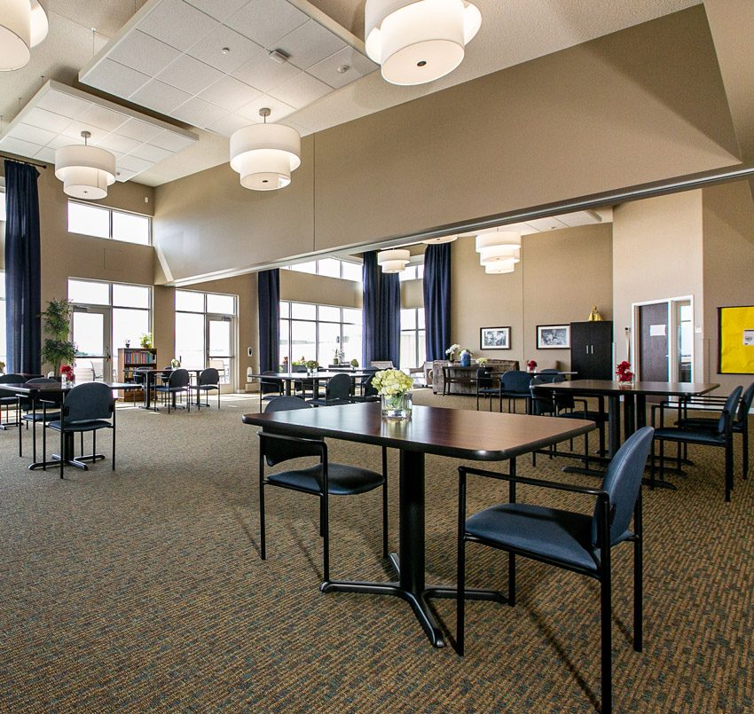 Hawkeye care center sitting area, with small rectangle tables each with two chairs spread across a large, open area.