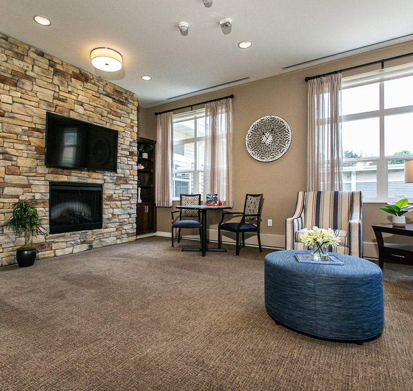 Hawkeye Care Center Living area with a TV placed over a fireplace on a brick wall, small table with two chairs, a striped arm chair, and blue round foot rest