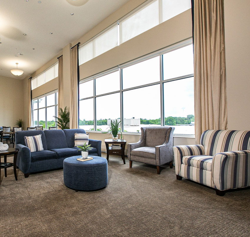 Hawkeye Care Center sitting area, with a blue couch, gray arm chair, blue and white striped arm chair, and floor-to-ceiling windows
