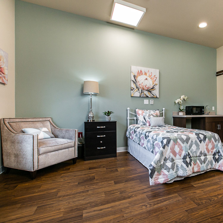 Hawkeye Care Center bedroom with a beige armchair in a corner, a nightstand with a lamp and plant next to it, a twin bed, and counter space with a microwave, sink, and lower cabinets