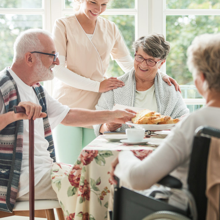 A group of 3 elderly residents having breakfast at a table with a nurse nearby
