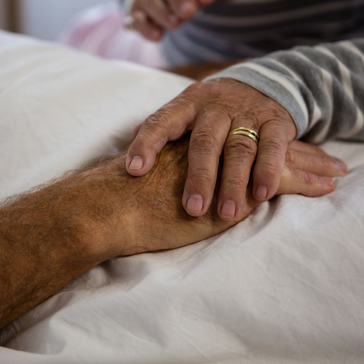 A close up of an elderly couple's hands, on top of each other